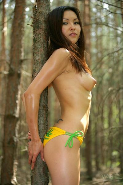 Shaved pussied skinny asian Annie Ling strips out of her yellow bikini in the forest