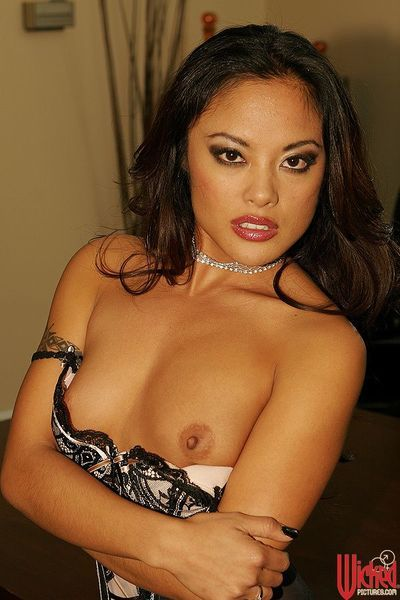 The erotic corset and tiny panty are wrapping the Asian babe Kaylani Lei's body