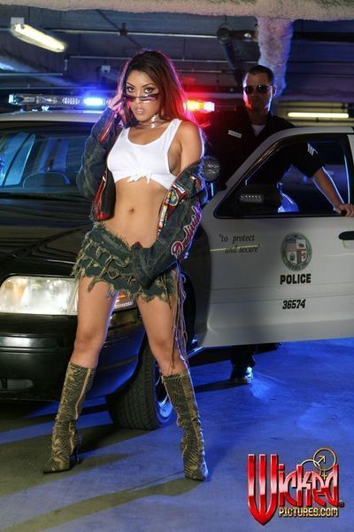 The salacious Asian girl Nautica Thorn is posing half naked against the police car